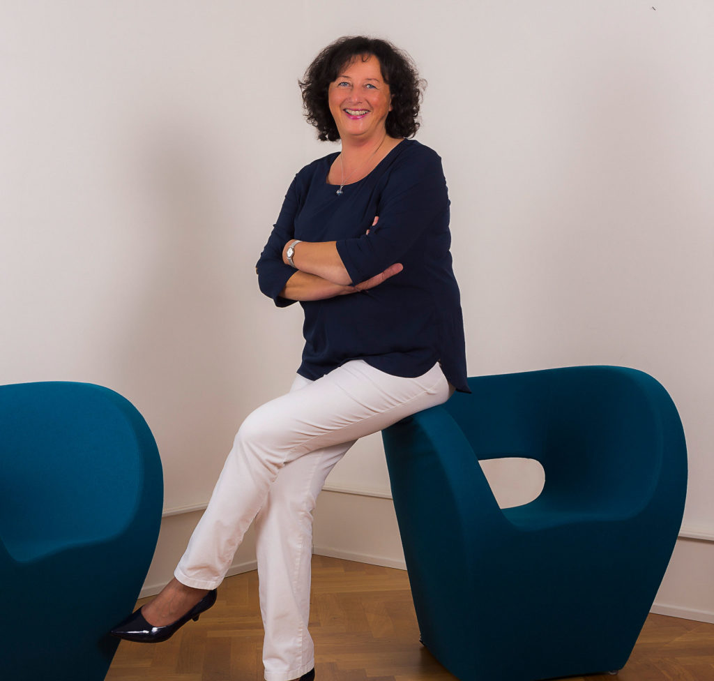 Birgit Preuß-Scheuerle sitzt auf Sessel und lächelt freundlich